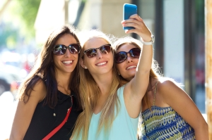 Outdoor portrait of group of friends taking selfie in the street.
